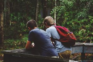 Two friends standing in a forest